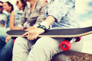 close up of female hand holding skateboard