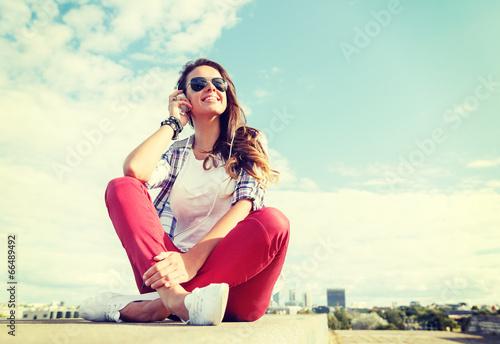 smiling teenage girl in eyeglasses with headphones
