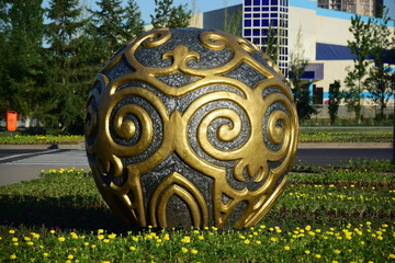 A decorative sphere on a flowerbed