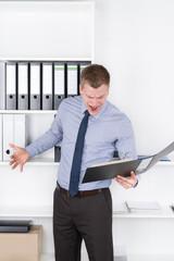 Wütender Mann schaut in einen Aktenordner im Büro
