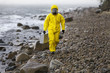 specialist in protective suit walking on rocky beach