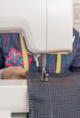 Sewing machine needle and seamstress on backgroud