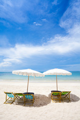 Beach chairs on the white sand beach with cloudy blue sky