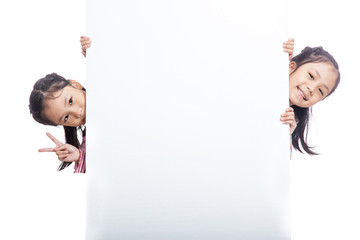 Asian twin sisters  peeking behind empty billboard
