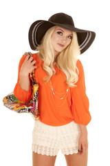 woman orange blouse hat purse smile close