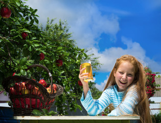 Girl in apple orchard drinks juice