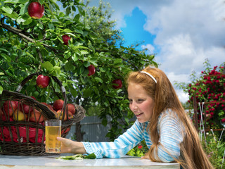 Girl near the apple tree with a glass of juice