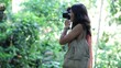 Woman taking photo of ancient sculpture in the forest