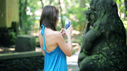 Woman taking photo with cellphone of ancient sculpture, Ubud
