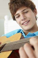 Teenage boy playing acoustic guitar