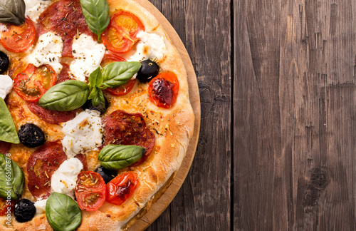 Rustic pizza with salami, mozzarella, olives and basil on wooden плакат