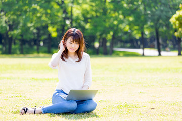 young asian woman using computer in the park