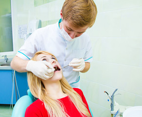 Dentist examining young adult patient