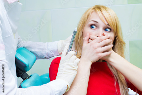 canvas print picture Young patient in dentist office, afraid of anesthetic injection