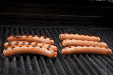 Hot dogs cooking on a grill