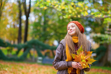 Young girl with bunch of leaves on a fall day