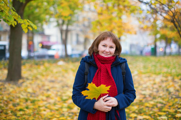 Cheerful girl in warm red scarf enjoying fall day