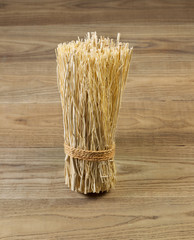 Tied bundle of straw on rustic wood