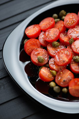 Salad with red tomatoes, capers, sea salt and black pepper