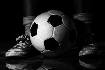 Dirty sneakers with soccer ball