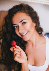 Portrait of woman eating strawberry