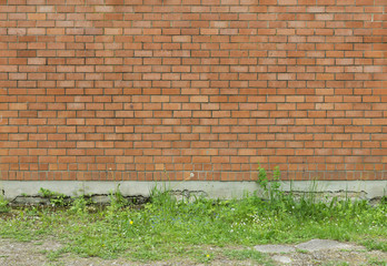 Wall from a red brick with a corrugated pattern with grass as ba
