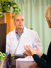 Mature  doctor listening with  female patient in clinic