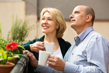 Mature couple on balcony with coffee