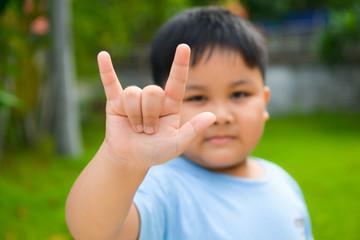 Cute boy show love hand symbol