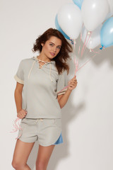 Beautiful girl with balloons on a white background