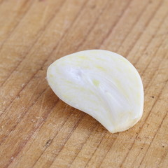 Close - up Sliced garlic on brown wood
