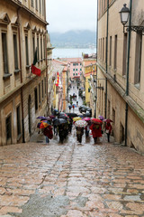 Tourists walking up stairs in street, Portoferraio, Italy