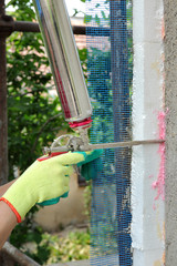 Worker apply polyurethane expanding foam glue with applicator