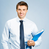 Portrait of business man with folder, over blue