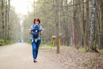 Young mother walking in forest with her baby