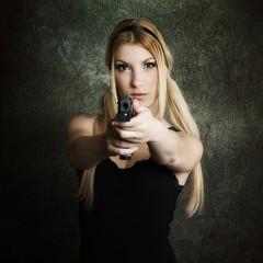 junge schöne Frau hält eine rauchende Waffe