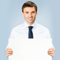 Business man showing blank signboard, over blue