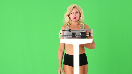 Unhappy young woman weighing self on scales
