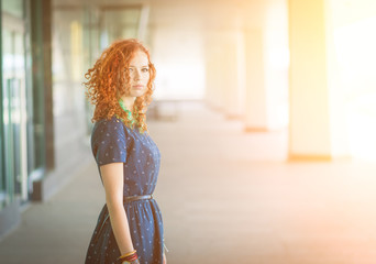 Portrait of a beautiful redhead girl. With sunshine.