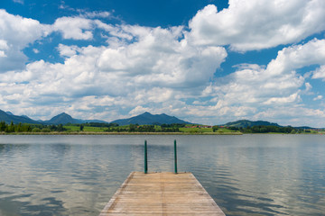 wooden boardwalk into lake hopfen in bavaria at sunny blue sky