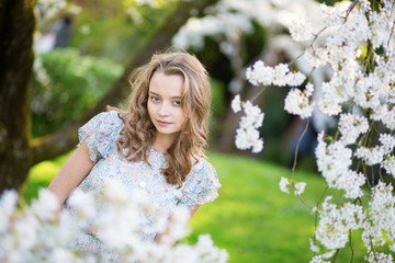 Young woman in blooming cherry garden