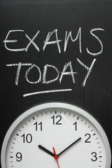 Exams Today written on a blackboard above a clock