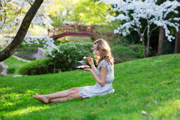Young European woman eating sushi in Japanese park