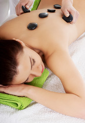 Beautiful woman on spa salon having stone massage.