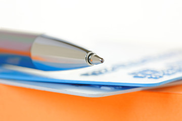 Pen and Credit Cards on an Orange Note Pad