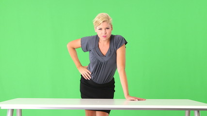 Seductive businesswoman standing by desk