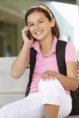 Pre teen girl with phone at school