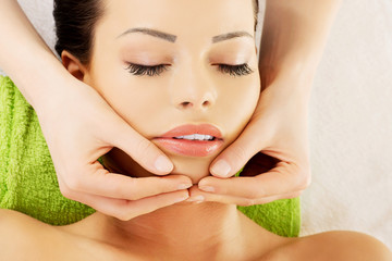 Relaxed woman enjoy receiving face massage