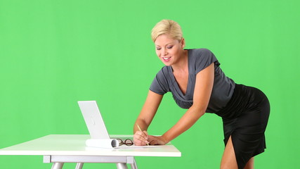 Provocative businesswoman standing by desk and using cellphone