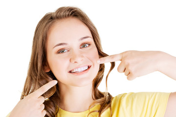 Teen girl pointing on her perfect teeth
